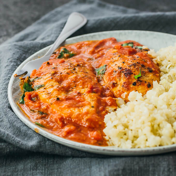 Chicken breasts with tomato sauce served on a plate with low carb cauliflower rice