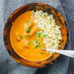 Easy indian butter chicken served with low carb cauliflower rice in wooden bowl