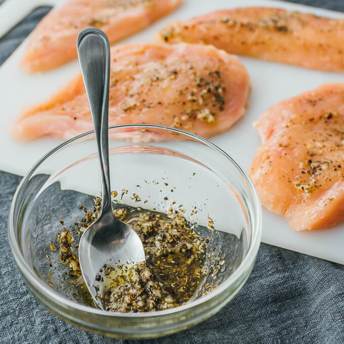 spreading oil and flavorings over chicken breasts