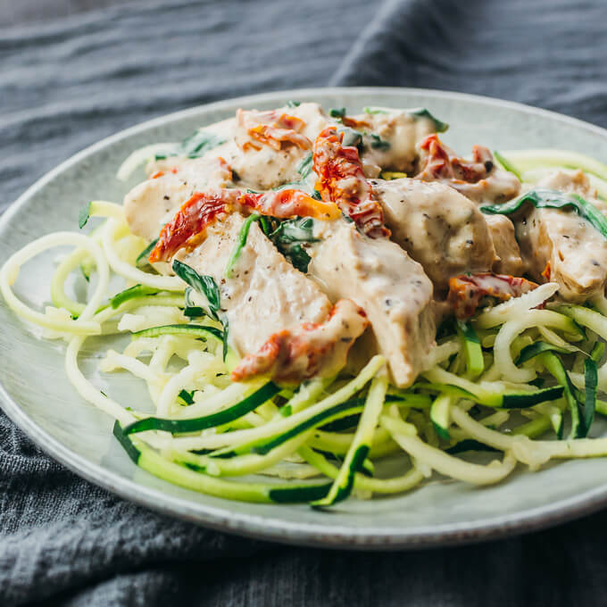 Easy Instant Pot creamy chicken dinner served with sun-dried tomatoes and spinach over a bed of zucchini spaghetti noodles