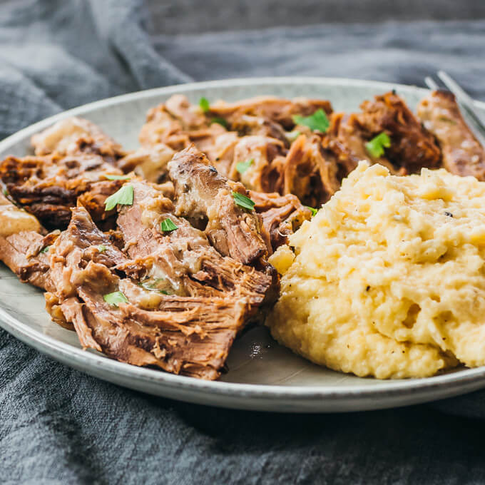 Instant Pot boneless leg of lamb served on a plate with mashed cauliflower