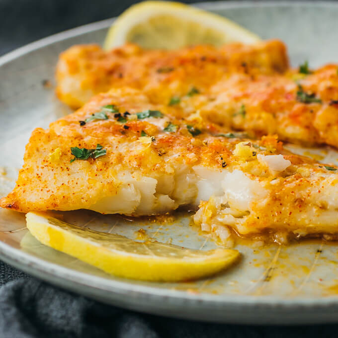 Lemon baked cod served on a plate and flaked