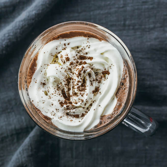 Overhead view of low carb hot chocolate in a glass mug topped with whipped cream and unsweetened cocoa powder