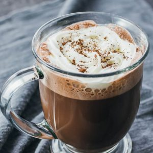 Low carb hot chocolate with almond milk served in a glass topped with whipped cream