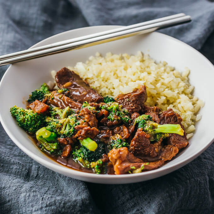 Instant Pot beef and broccoli served in a white bowl with cauliflower rice