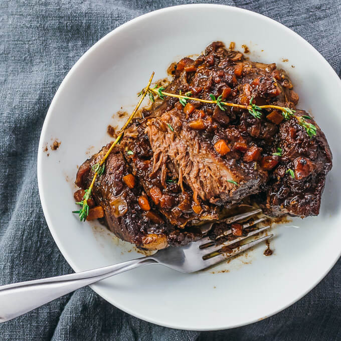 Overhead view of low carb instant pot short ribs on a white plate with a fork