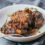 Instant Pot boneless beef short ribs with red wine and balsamic sauce served in a white bowl topped with fresh thyme
