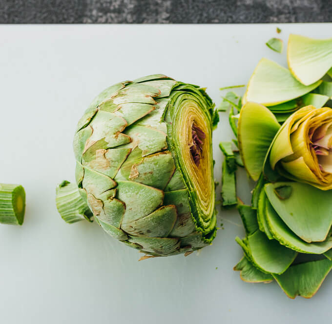 trimming off ends of artichoke