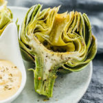 close up view of microwaved artichoke served on plate