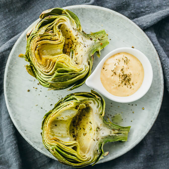 Steamed artichokes on a plate with dip