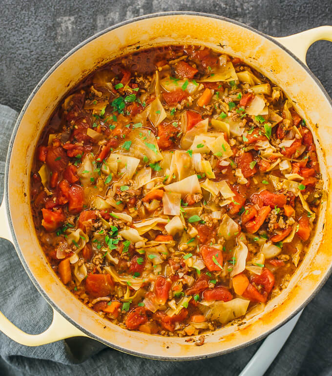 Unstuffed cabbage rolls soup in a yellow dutch oven pot with ground beef and tomatoes