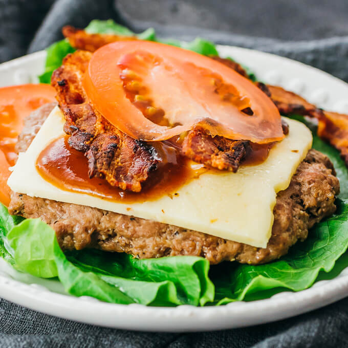 pressure cooker burger topped with cheese bacon tomatoes and bbq sauce