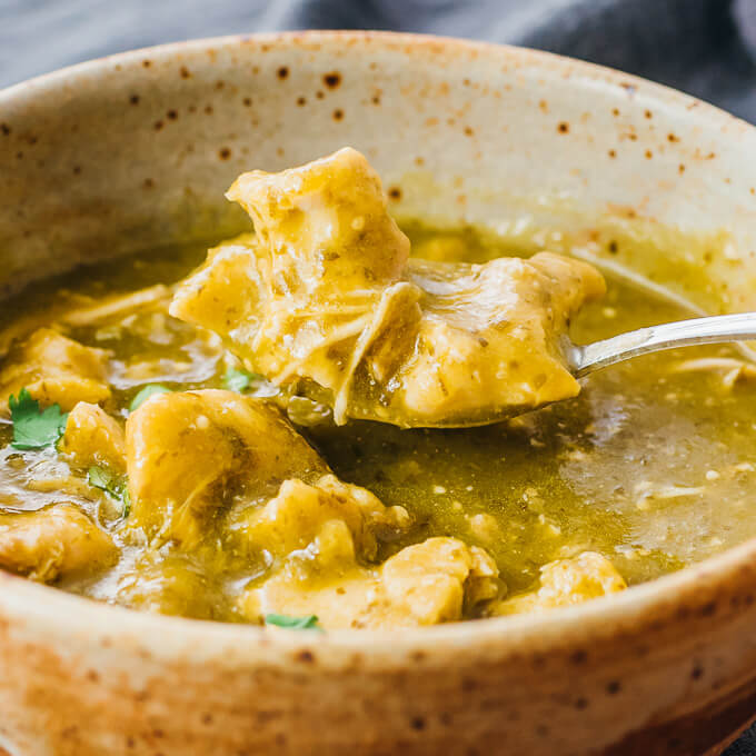 scooping up chili verde chicken with spoon