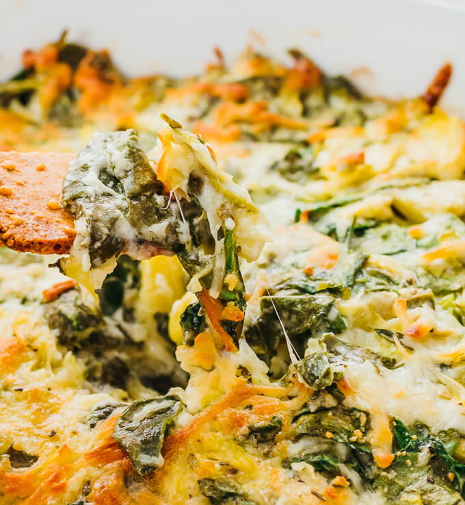 showing off how creamy this homemade spinach artichoke dip is