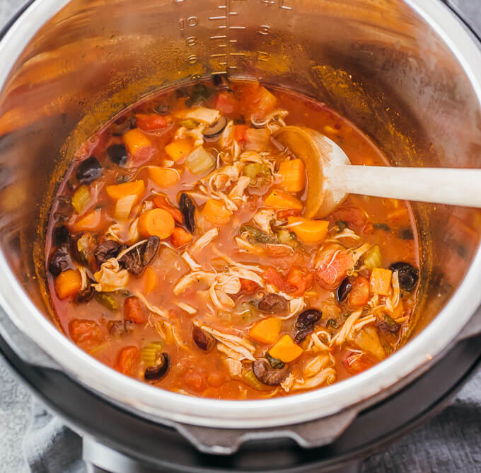 stirring italian chicken stew and vegetables in the electric pressure cooker pot
