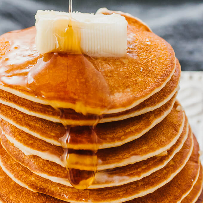 tall stack of low carb almond flour pancakes with butter and sugar free syrup