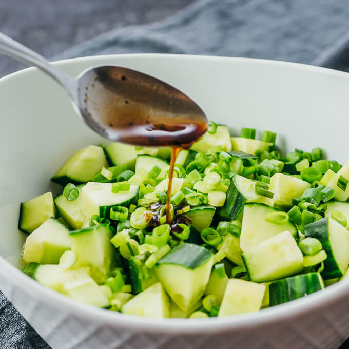 pouring dressing over keto friendly japanese cucumber salad
