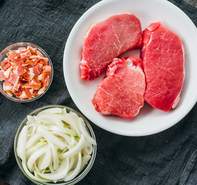 recipe ingredients including diced bacon, sliced onions, and boneless pork chops