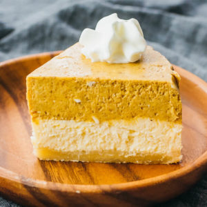 slice of pumpkin cheesecake on wooden plate
