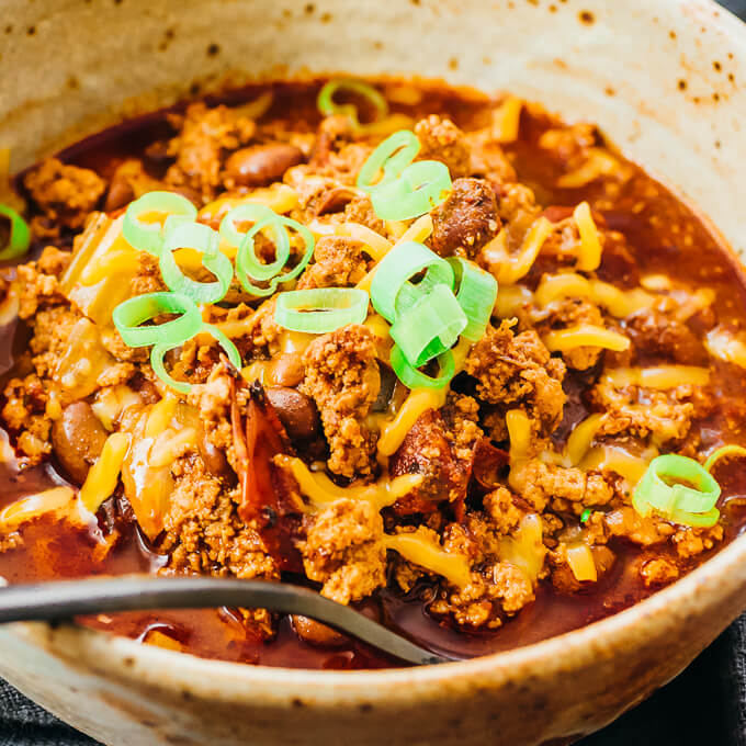 instant pot turkey chili topped with cheddar cheese and scallions