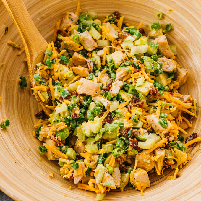 tossing keto chicken salad with low carb ingredients in a wooden bowl