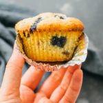 close up view of keto blueberry muffin with wrapper open