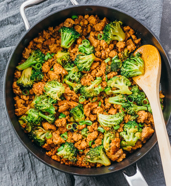 cooking pork stir fry with broccoli in black pan