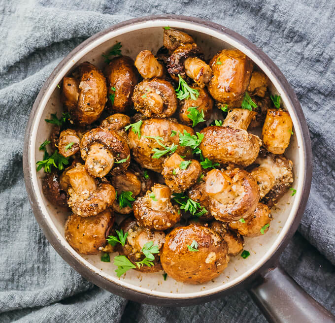 low carb baked mushrooms in a bowl topped with parsley