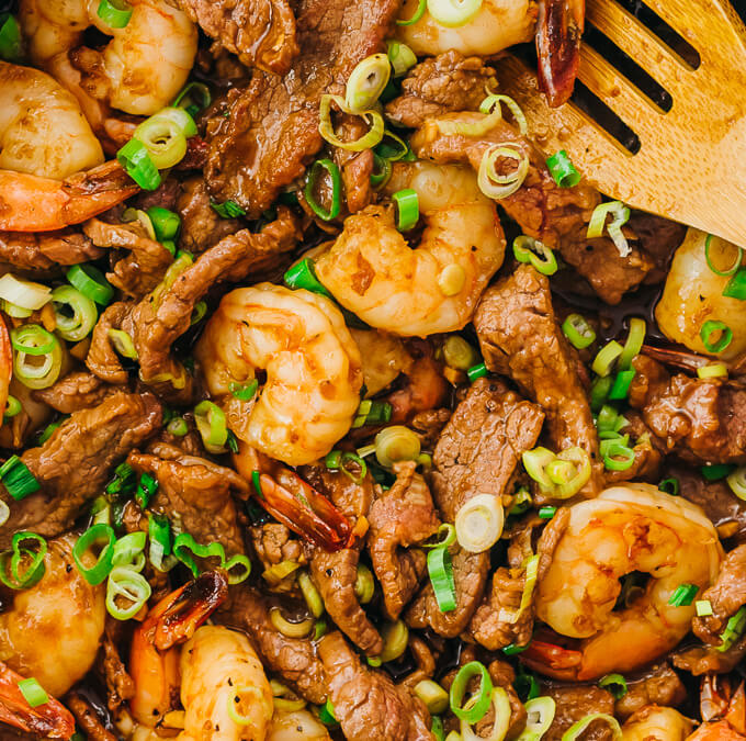 overhead view of asian surf and turf with stir fry sauce and scallions