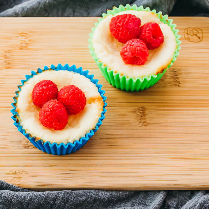 two mini keto cheesecake bites in cupcake lners on wooden plate