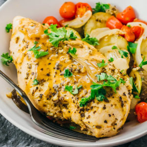 close up view of baked chicken with vegetables