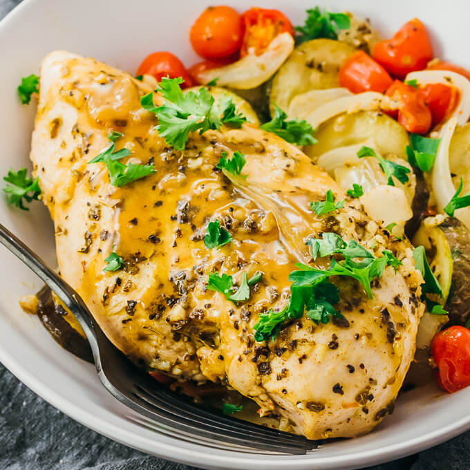 baked greek marinated chicken served in a white bowl