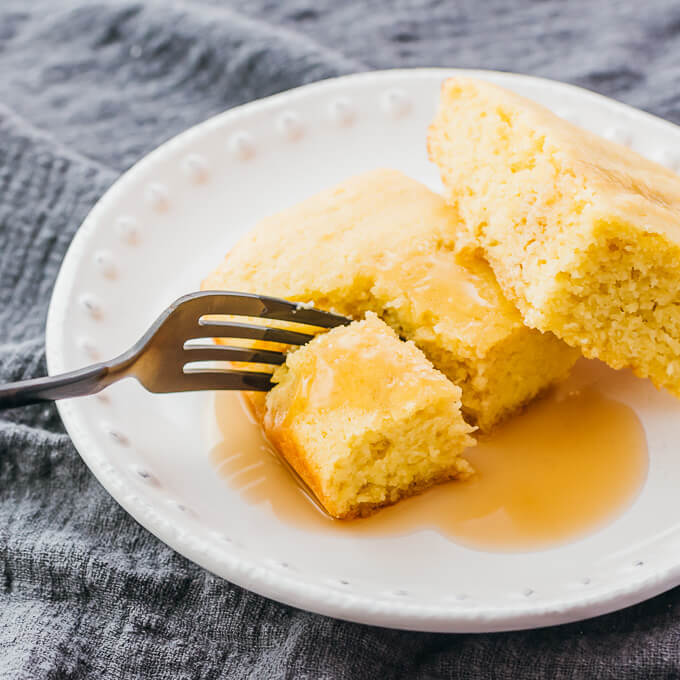 cutting a bite sized piece of gluten free cornbread with a black fork