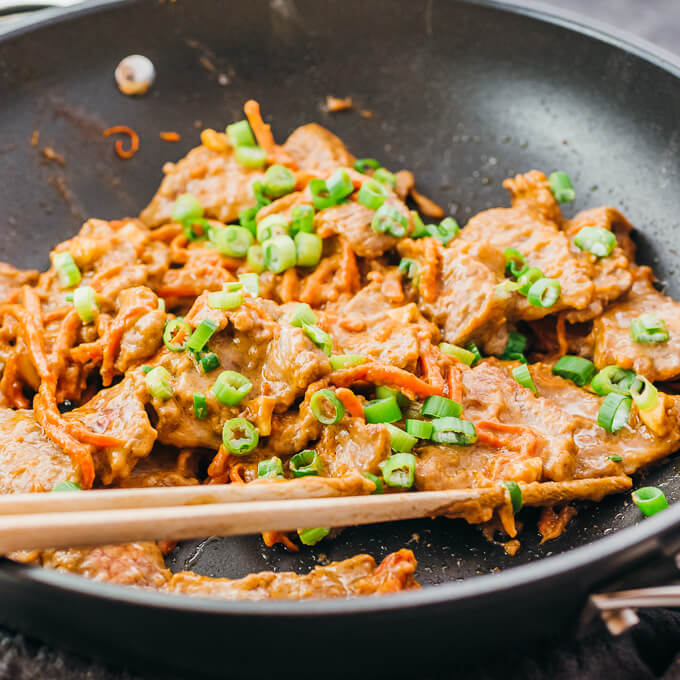 using chopsticks to stir beef stir fry with scallions and peanut sauce