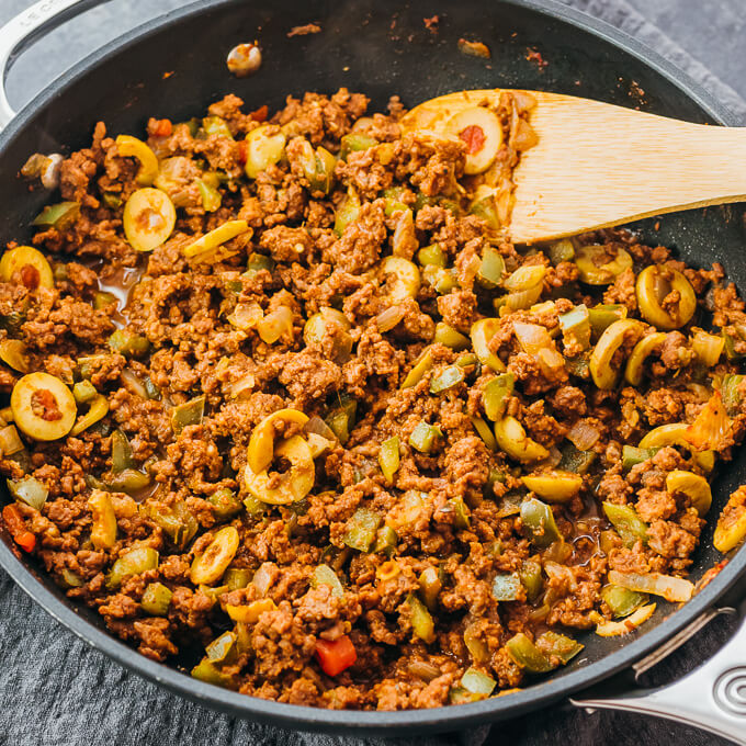 cuban picadillo with ground beef and olives cooking in a nonstick pan