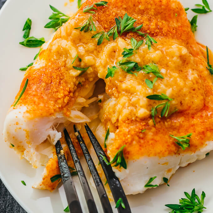 flaking a baked cod fillet with a fork
