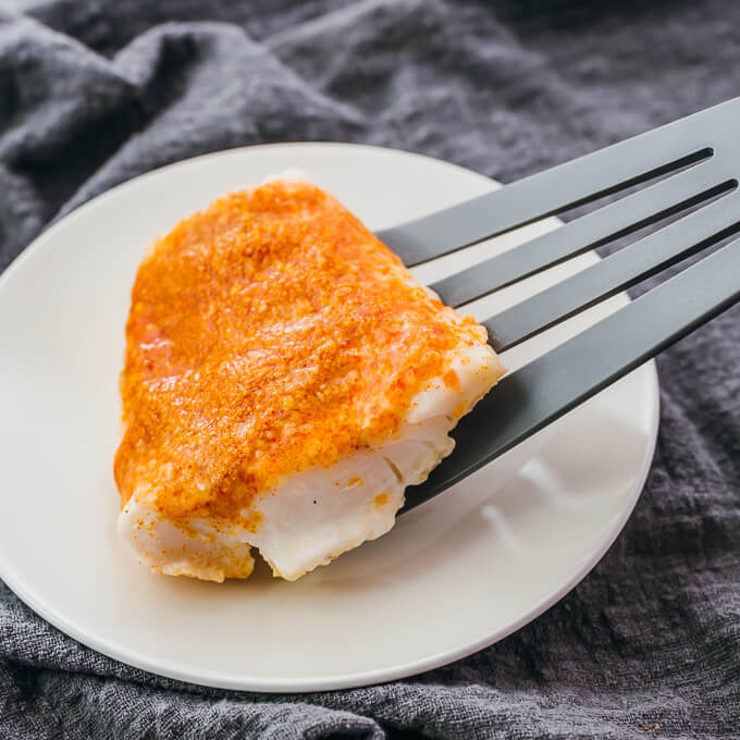 serving baked cod onto a plate