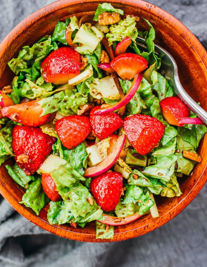 overhead view of summer strawberry salad in wooden bowl