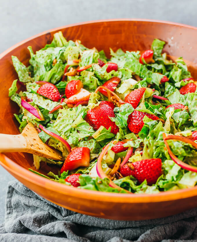 mixing fresh strawberry salad with balsamic dressing
