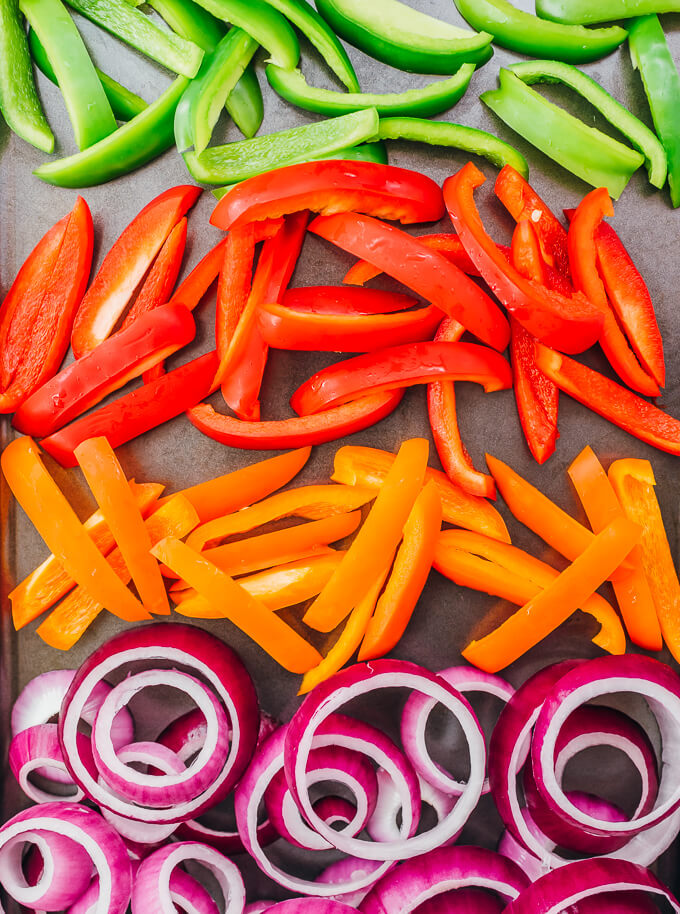 sliced bell peppers and onion rings on sheet pan