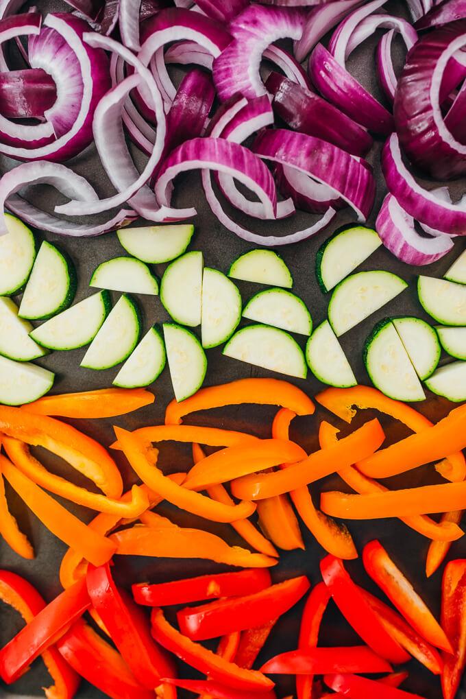 sliced vegetables on a baking sheet before roasting