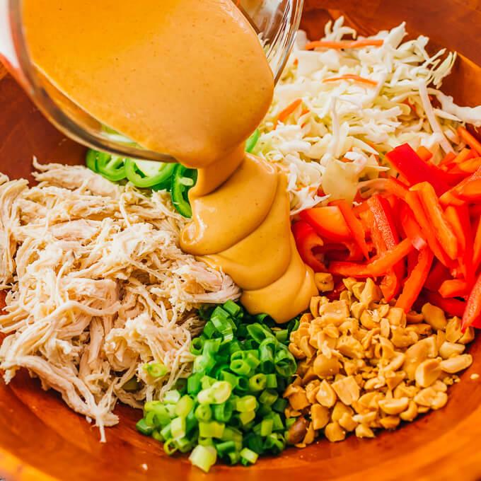 pouring peanut sauce over thai salad