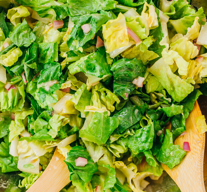 tossing romaine lettuce with red wine vinaigrette