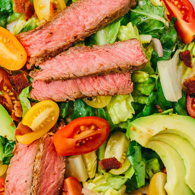 steak with bacon and avocado over romaine salad
