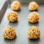 cheese balls covered in bagel seasoning on a sheet pan