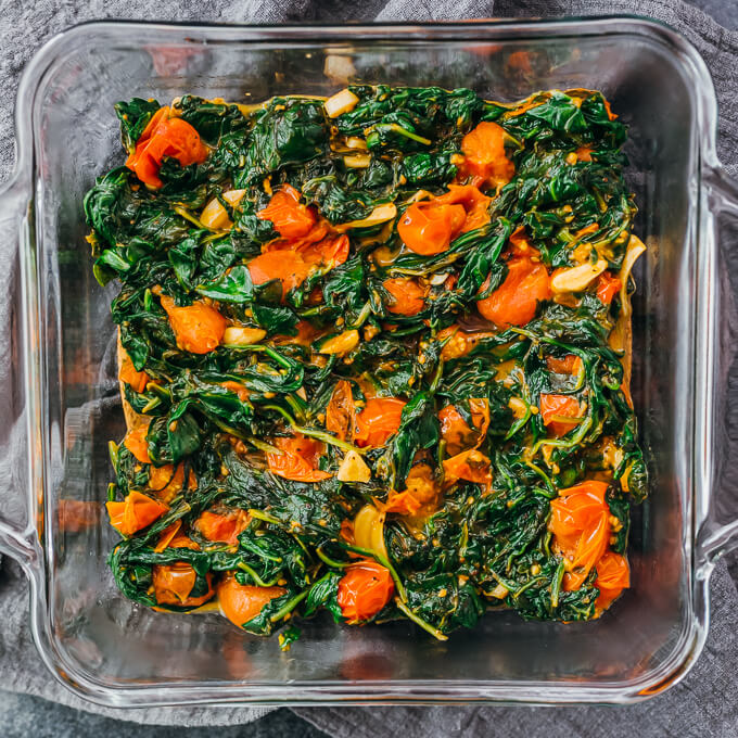 cooked spinach and tomatoes in baking dish