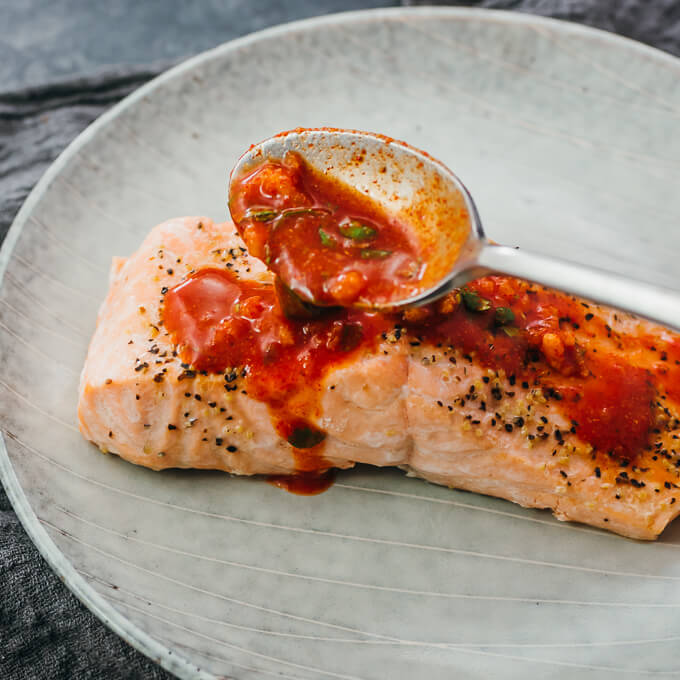 spooning chili lime sauce over cooked salmon