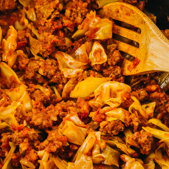 stirring ground beef with cabbage and tomatoes