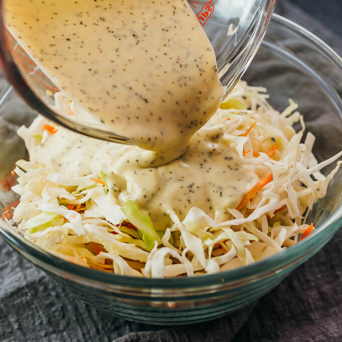 pouring dressing over coleslaw mix