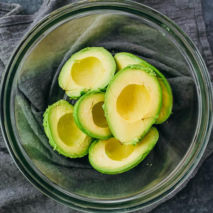 avocado halves in glass bowl